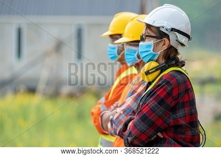 Group Of Asian Engineers Wearing Protective Mask To Protect Against Covid-19 With Helmet Safety In T