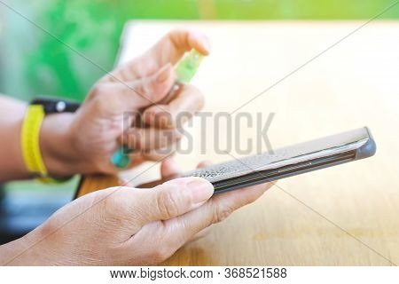 Hands Of Woman Cleaning Smartphone With Alcohol Spray To Prevent Infection Of Corona Virus (covid-19