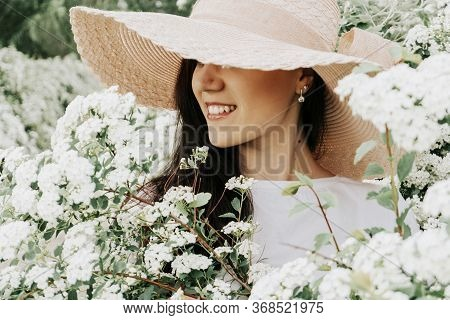 Girl Hides Her Face Behind A Hat On A Background Of Flowers. Young Woman In A Pink Straw Hat On Natu