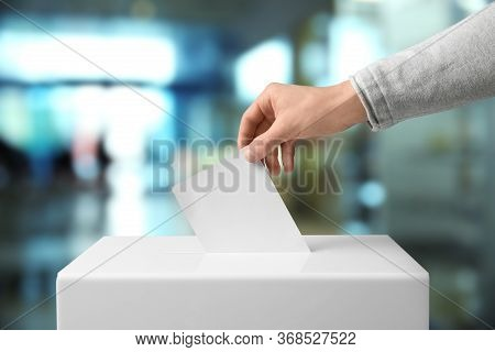 Man Putting His Vote Into Ballot Box Indoors, Closeup