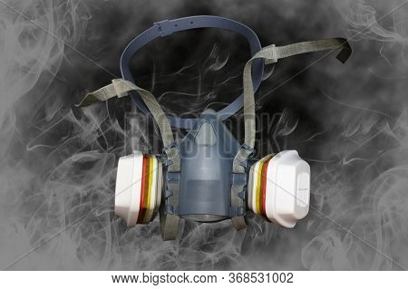 Half Mask Respirator Or Gas Mask With Antivirus Filters On A Dark Background With Smoke Around.