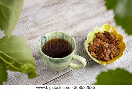 Ceramic Cup Of Healing Beverage Of Birch Mushroom Chaga, Bowl Of Mushroom Pieces On Light Wooden Bac