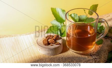Glass Cup Of Healing Beverage Of Birch Mushroom Chaga, Mushroom Pieces, Birch Twig On Wooden Plank O