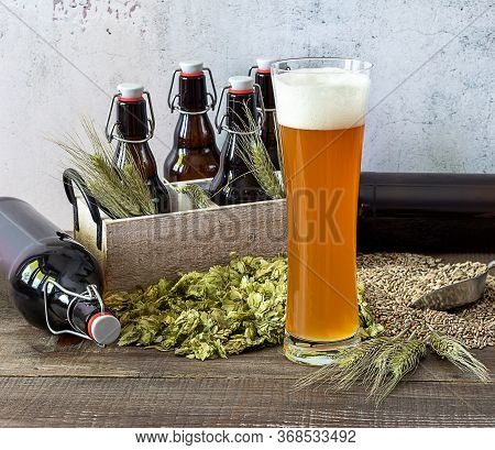 Wheat Craft Beer In High Glass With Wheat, Hops And Bottles. Typical German Style. Micro Brewing Con