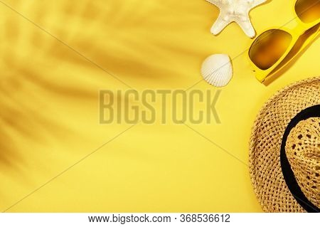 Summer Background With Leaves Shadows. Straw Hat, Sunglasses, Shell And Starfish On Yellow Surface.