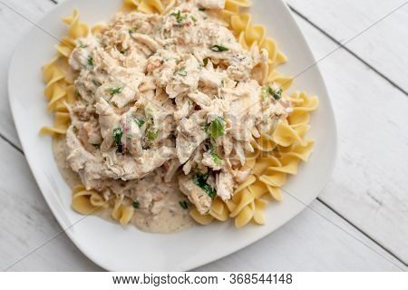 Crack Chicken Slow Cooked Dish Over Egg Pasta On A White Plate. Creamy Chicken With Cream Cheese Sau