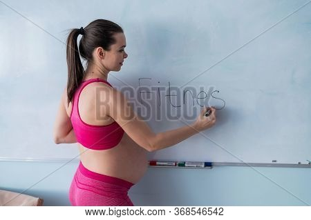 A Pregnant Woman In Sportswear Writes The Word Fitness On A White Marker Board. A Girl In The 3rd Tr