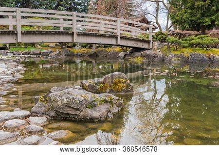 Kelowna, British Columbia/canada - April 28, 2018: Mossy Rocks And Bridge Over The Koi Pond At Kasug