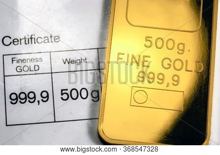 Minted Gold Bar Weighing 500 Grams On Paper Certificate Background. Gold Ingot With Assay Certificat