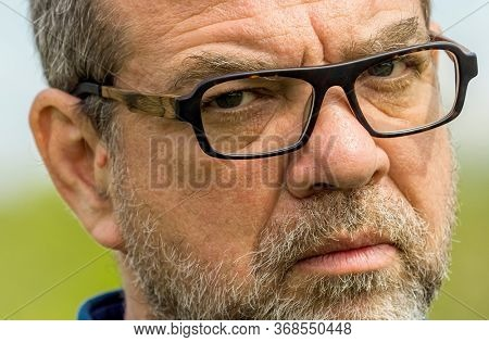 Serious unshaven adult man with glasses outdoors close-up portrait