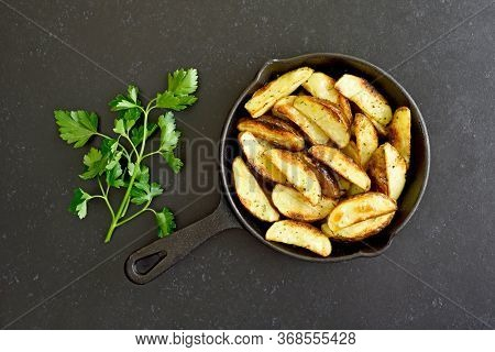 Fried Potato Wedges In Frying Pan On A Over Black Stone Background. Vegetarian Food. Top View, Flat