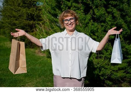 A Happy Elderly Woman With Glasses Stands In A Park And Holds Paper Bags. Female Retired Shopaholic