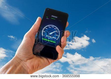 5g Network Speed Concept. Man Checking His Smartphone On Network And Making A Speed Test.