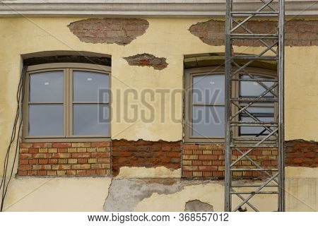 Overhaul Of The Light Yellow Stucco Facade Of An Old Historically Building With Scaffolding In The C