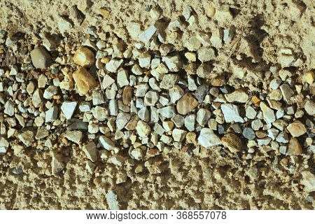Small Stones On The Sand. The Shore Of The Reservoir Of Pebbles, Rubble. Sea Rocky Beach. The Textur