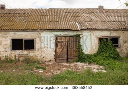 An Old Barn With A Wooden Barn Door In An Agricultural Farm. Barn With Vibrant Green Wall And Old Wo