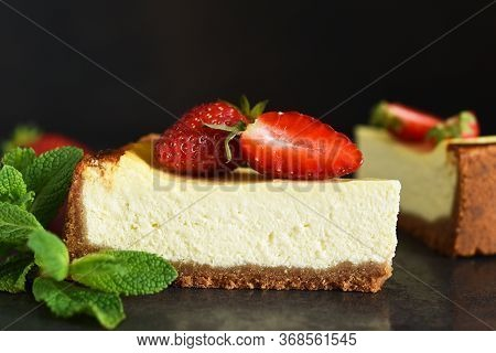 Slice Of Cheesecake With Strawberries And Mint On A Dark Background. Cheesecake New York. Advertisin