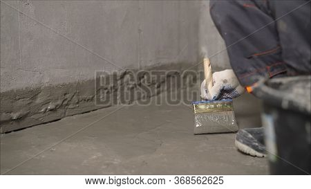 Waterproofing Mortar On A Concrete Floor. A Worker Applies Waterproofing To A Concrete Floor With A