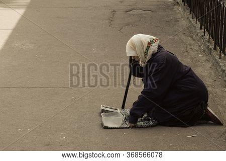Chernihiv, Ukraine, June 7, 2019. An Elderly Woman In A Scarf Beg For Money, Kneeling On A City Stre
