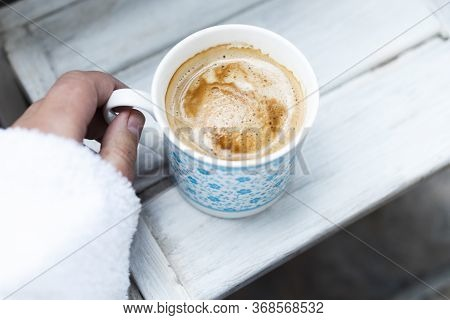 Cropped Female Hand And Cappuccino Coffee In A Cup On A White Wooden Table. Top View, Copy Space.