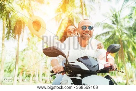 Laughing Happy Couple Travelers Riding Motorbike During Their Tropical Vacation In Thailand Under Pa
