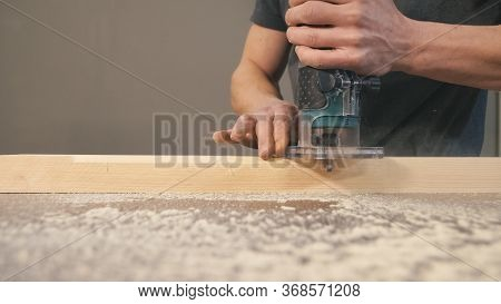 Worker Bevel Wooden Board. Milling Cutter And Sawdust, Closeup. Professional Carpentry Concept With