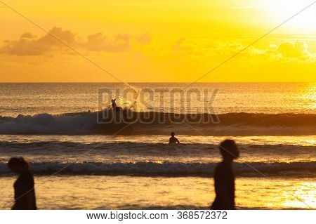 Magical Dramatic Sunset On A Tropical Beach. Surfer With A Board Jumping Out Of A Wave. Seascape, Oc