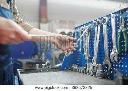 Close-up of unrecognizable repairman choosing work tool on workbench in modern workshop