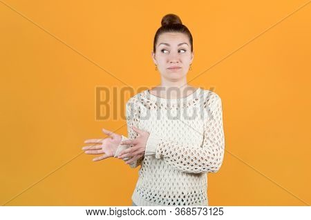 The Girl Holds Out Her Hands To Take Something, But Looks Doubtful. Isolated On Yellow