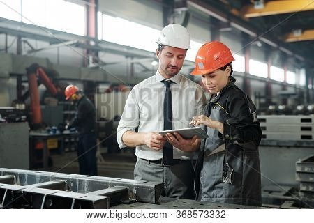 Asian metalworking specialist discussing technical sketch with engineer while they using engineering app on tablet