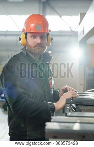 Portrait of brutal man in workwear and ear protectors working with metal pieces in factory shop