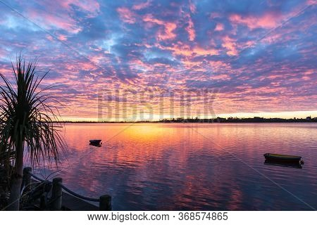 Stunning Tauranga Sunrise With Low Cloud Colored Pink And Blue Reflected In Calm Water Below.