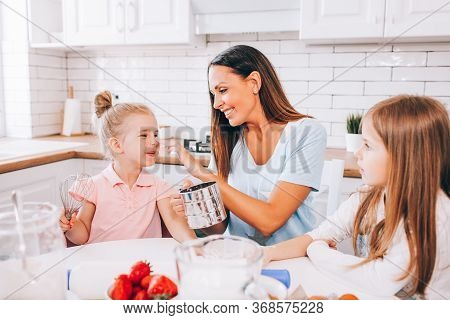 An Attractive Smiling Family Of Mother And Two Daughters Baking In A Light Kitchen At Home. Sibling