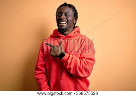 Young african american sporty man wearing sweatshirt with hoodie over yellow background cheerful with a smile of face pointing with hand and finger up to the side with happy and natural expression