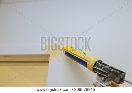 Worker Hands Applying Silicone Sealant With Caulking Gun For Repairing Door Molding Trim