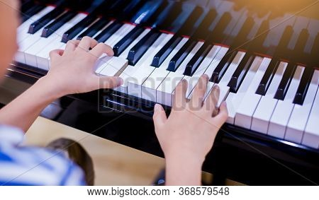 Selective Focus To Kid Fingers And  Piano Key To Play The Piano.