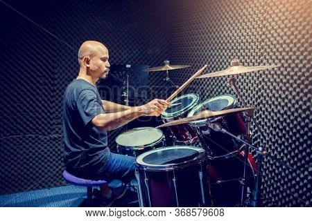 Asian Man Put Black T-shirt To Playing The Drum Set With Wooden Drumsticks In Music Room , The Conce