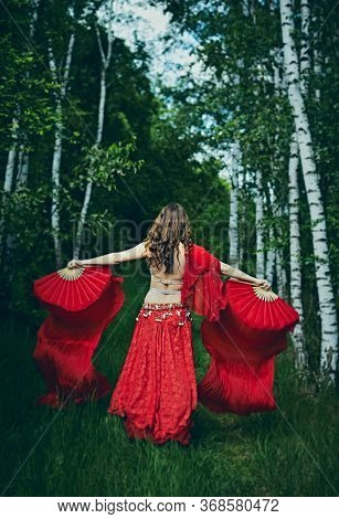 Young belly dancer  training her choreography among the trees. Outdoor activities in a new normal