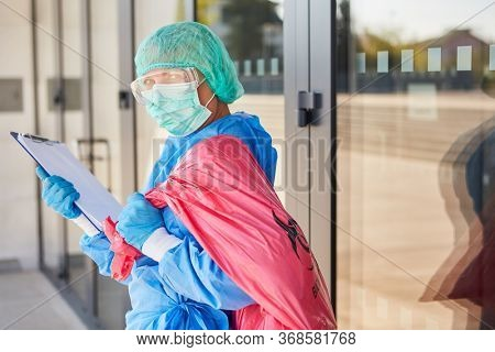 Cleaner with checklist when checking the disposal of hazardous waste in clinic during coronavirus pandemic