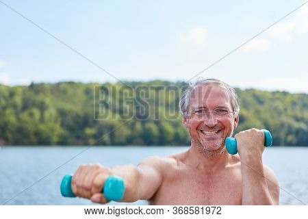 Vital senior in nature on the shore of the lake trains with dumbbells for fitness and strength