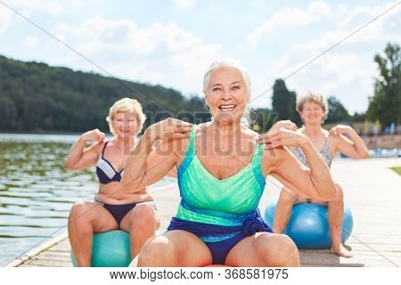 Vital senior with gymnastic ball makes back training with friends at the lake