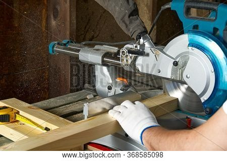 Closeup Of Professional Cabinet Makers Working With Electric Circular Saw At Woodworking Workshop. S