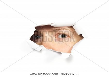 Young Woman Peeping Through Hole On Paper. Female Eye Looking Through Hole. Isolated On White Backgr