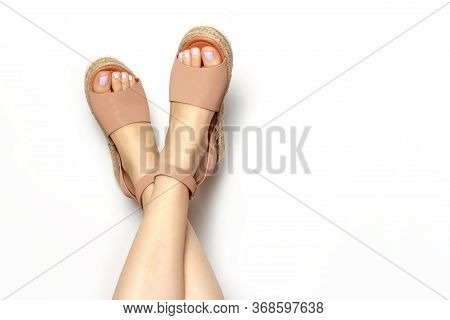 Female Legs With White Pedicure In Summer Brown Sandals, On A White Background, Copy Of The Space