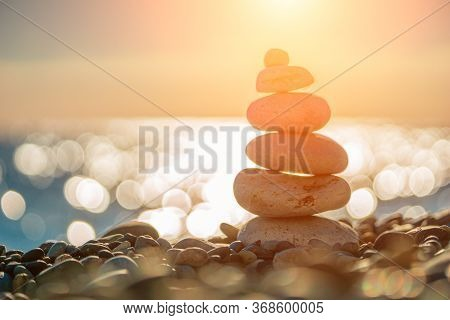 Balanced Pebbles Pyramid On The Beach On Sunny Day And Clear Sky At Sunset. Blue Sea On Background S