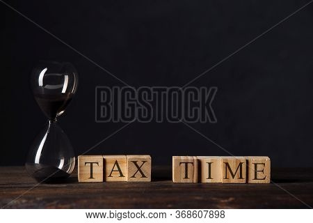 Hourglass Or Sandglass On Cube Wooden Block With Alphabets Tax Time On Wood Table In The Dark Room.t