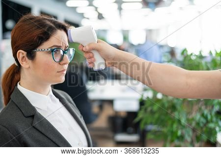 Temperature Measurement By Electronic Infrared Thermometer For Office Staff. Unhappy Woman With A Fe