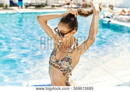 Pretty Woman In Swimsuit And Sunglasses Sunbathing Near Swimming Pool At Hot Summer Day.