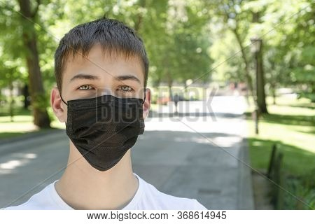 Teenage Boy In Medical Protective Black Mask In An Empty City Park With Green Grass And Trees Next T