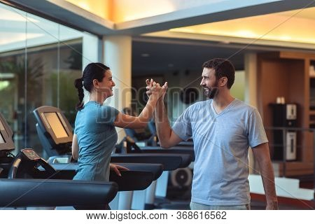 Personal Trainer Working With Client In Gym. Trainer Man Giving Rewarding Hive Five To Young Pretty
